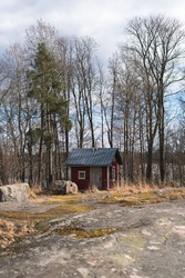 A red shack with bare trees in the background