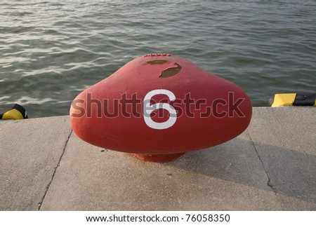 a red ship bollard on the dockside with the number 6 painted on it