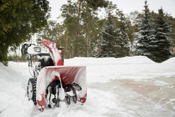 A red snow-covered snow blower stands on the road after clearing the area. Clearing the area from snowfall.