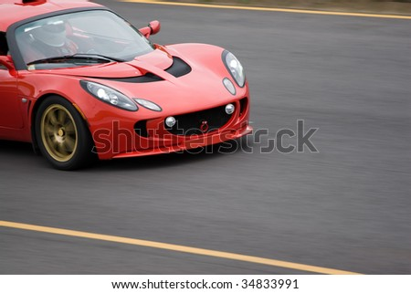 A red sports car speeding down the road.