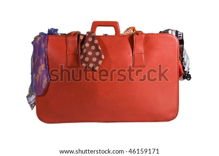 A red suitcase filled with colorful clothes isolated on white