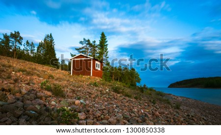 A red Swedish fishermen house at the shore with a dramatic cloudy blue sky.