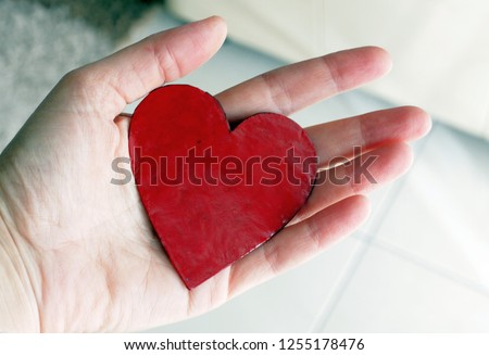 A red symbolic heart of a cardboard hold in a hand #1255178476