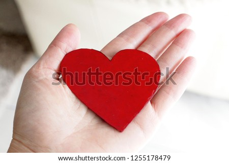 A red symbolic heart of a cardboard hold laying on a hand #1255178479
