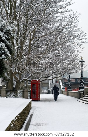 A red telephone box beside a walkway, on a cold Winter's day, London, England.