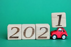 A red toy car is carrying blocks with the numbers 2021. The new year 2021 is approaching. Happy New year. Copy space.