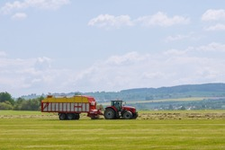 A red tractor rakes dry grass and places hay for loading and hauling.
