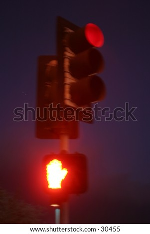 a red traffic light also has a no crossing symbol attached and activated at the same time in this special time laps (bulb exposure) image at night