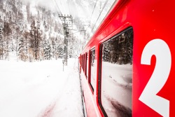 A red train in the middle of a desert of snow