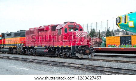 A red train sits on the tracks in a rail yard