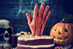 a red velvet cake topped with a bloody hand in a scary scene for halloween with a carved pumpkin, a skull and cobwebs