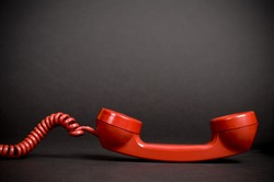 A red vintage telephone receiver with a spiral cord.