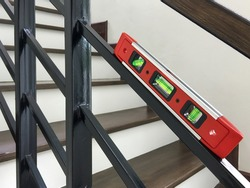 a red water level gauge on rail guard of a stair