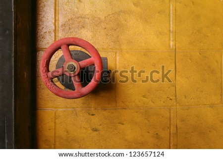 a red water valve on a yellow wall - stock photo