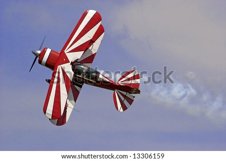a red-white  biplane at an air show.