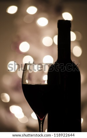A red wine and bottle silhouette with de-focused lights in background. - stock photo