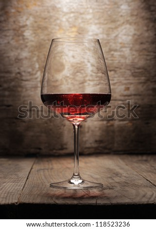 A red wine glass on wooden background