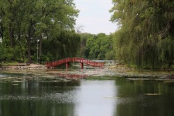 A red, wood, arched bridge over a lake leading from a park to the woods in Janesville, Wisconsin, USA
