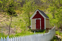 A red wooden clapboard building with white trim. The old shed has a horseshoe over the wooden door pointing upwards. There's a rusty lock on the door. The vintage storage building is among lush trees.