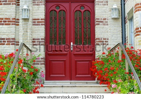 A red wooden door graces the entrance to a home.