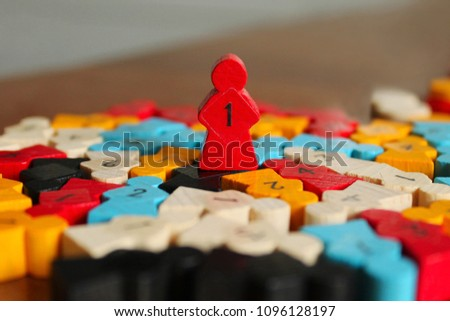 A red wooden figure in the shape of a man stands on other details. Parts of the board game. Leadership skills. Number one, winner and losers. Back and front background in blur.