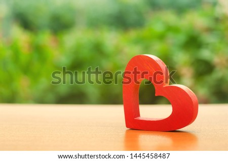 A red wooden heart on nature background. The secret of relationships and the rules of a strong family. Strong love affair. Secrets, rumors and gossip. concept of female intimate health. Heart health