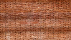 A reddish brown laterite brick wall. Attractive texture of red brick wall for background design with copy space. Selective focus