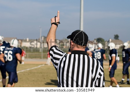 A referee signals a first down for a team of players - stock photo