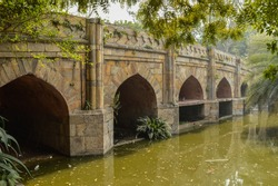 A reflection and mesmerizing view from the side of the pond,lake of palm trees and bridge monument at lodi garden or lodhi gardens in a city park at winter foggy morning.