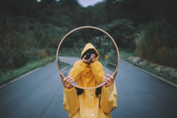 A reflection in a mirror of a man in a yellow raincoat with a camera