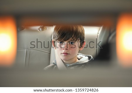 A reflection of a young boy from the front seat of a car's Passenger Vanity Mirror. Child buckled into his seat belt in the back seat of a vehicle. Young male with his seat belt on.
