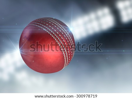 A regular red cricket ball flying through the air on an indoor stadium background during the night