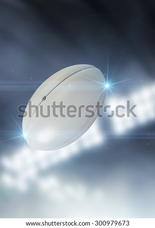 A regular rugby ball flying through the air on an indoor stadium background during the night