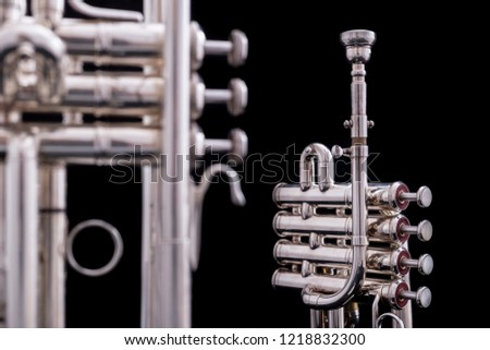 A regular silver plated Bb trumpet with a silver plated piccolo trumpet on a black background. The piccolo trumpet is usually played in baroque music.