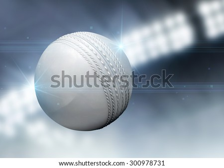 A regular white cricket ball flying through the air on an indoor stadium background during the night
