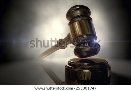 A regular wooden auctioneers hammer or judges gavel with copper trim backlit on a dark background