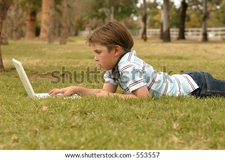 A relaxed child seen studying or playing on his laptop computer - wireless lifestyle