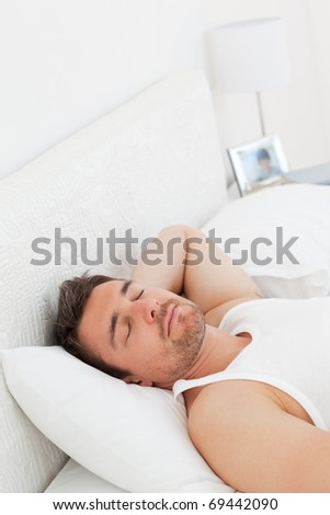 A relaxed man in his bed before waking up in his bedroom