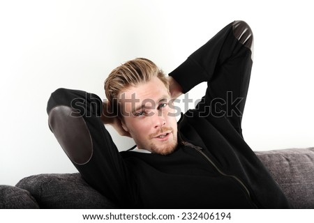 A relaxed young man wearing a black hoodie sitting down in a sofa, looking at camera. White background.