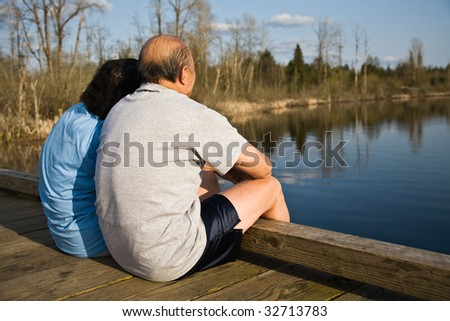 A relaxing senior asian couple sitting by the lake spending time together