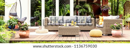 A relaxing spot for a warm, summer day - a stylish, wooden terrace with wicker garden furniture, cushions, plants and flowers #1136759030