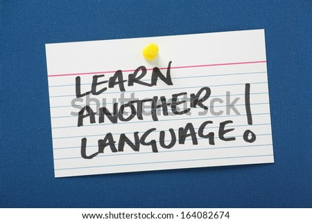 A reminder to learn another language written on a white note card and pinned to a blue notice board. A second language benefits our job prospects and helps business trade in a competitive market.