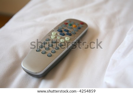 A remote control on a bed