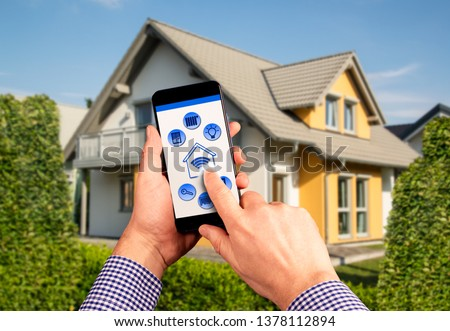 A remote control with icons for operating a smart home with house in the background