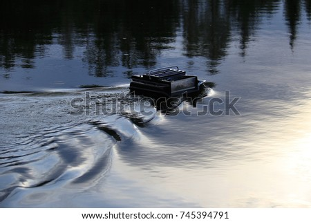 A remote controlled feeder boat in a lake used in recreational fishing. #745394791