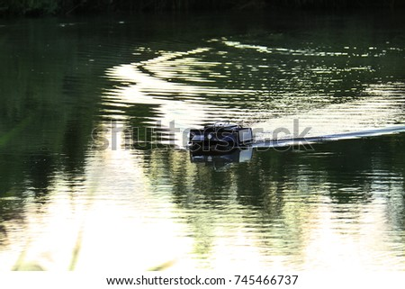 A remote controlled feeder boat in a lake used in recreational fishing. #745466737