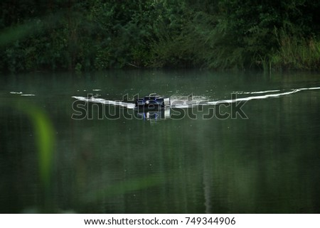 A remote controlled feeder boat in a lake used in recreational fishing. #749344906