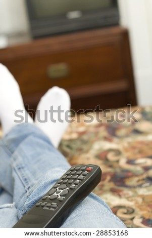 A remote controller sits on the lap of a person laying on a hotel bed.