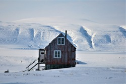 A remote wooden house in the bleak and frozen Arctic landscae of Kangerluk, Greenland