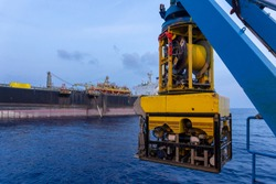 A Remoted Operated Vehicle (ROV) hanging on Launch & Recovery System (LARS) for underwater pipeline survey and inspection nearby Floating Storage Offloading (FSO) vessel.